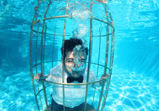 Funny groom underwater in a bird cage Stock Photography