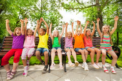Funny group of kids on bench with arms up Royalty Free Stock Photos