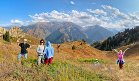 Funny group of people hiking on the meadow of mountain. Aerial view at mountain range and blue sky royalty free stock photography
