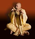 Funny Guru Casting a Spell. Funny guru sitting lotus style casts an evil spell Royalty Free Stock Photos
