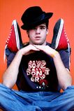 Funny Guy. Young man sitting with hands under chin, hat cocked sideways, red hightop shoes propped on his shoulder stock photo