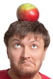 Funny guy with an apple on his head. Funny young student with an apple on his head Royalty Free Stock Photography