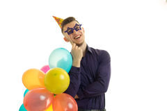 Funny guy with balloons in his hands and paper glasses laughs Stock Image
