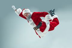 Funny guy in christmas hat. New Year Holiday. Christmas, x-mas, winter, gifts concept. Funny serious guy with christmas hat dancing at studio. New Year Holiday royalty free stock photography
