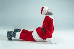 Funny guy in christmas hat. New Year Holiday. Christmas, x-mas, winter, gifts concept. Funny serious guy with christmas hat dancing at studio. New Year Holiday royalty free stock photos