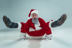 Funny guy in christmas hat. New Year Holiday. Christmas, x-mas, winter, gifts concept. Funny serious guy with christmas hat dancing at studio. New Year Holiday royalty free stock photo
