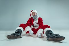 Funny guy in christmas hat. New Year Holiday. Christmas, x-mas, winter, gifts concept. Funny serious guy with christmas hat dancing at studio. New Year Holiday royalty free stock image