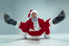 Funny guy in christmas hat. New Year Holiday. Christmas, x-mas, winter, gifts concept. Funny serious guy with christmas hat dancing at studio. New Year Holiday stock photos