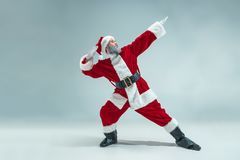 Funny guy in christmas hat. New Year Holiday. Christmas, x-mas, winter, gifts concept. Funny serious guy with christmas hat dancing at studio. New Year Holiday stock image