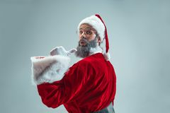 Funny guy in christmas hat. New Year Holiday. Christmas, x-mas, winter, gifts concept. Funny guy with christmas hat posing at studio pointing to camera. New Stock Photos
