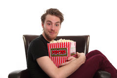 Funny guy holding a popcorn bucket sitting down Royalty Free Stock Image