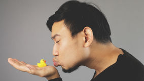 A funny guy kissing his rubber duck. An asian man with black t-shirt royalty free stock image