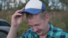 Funny guy in a plaid shirt and a baseball cap. He smiles cheerfully and lowers the baseball cap to his eyes. Looks like an American trucker stock video footage