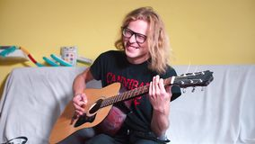 Funny guy playing an acoustic guitar. Funny guy plays acoustic guitar on a yellow background stock footage