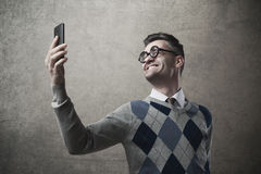 Funny guy taking a selfie. Funny guy with glasses taking a self picture with a smartphone Royalty Free Stock Image