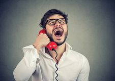 Funny guy on the telephone. Funny guy in glasses on the red telephone laughing out loud royalty free stock image