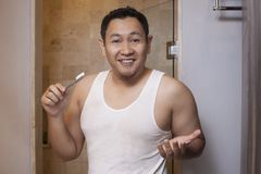 Funny Guy with Toothbrush in Bathroom. Portrait of funny young Asian male holding toothbrush in bathroom, smiling and shrug gesture indonesian malaysian thai royalty free stock photo