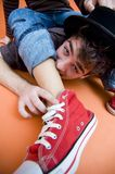 Funny Guys. Young man or teenager laying on floor biting on leg of another young male, red hightop shoe stock images