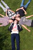Funny Guys. Group of teen guys laying in the grass royalty free stock images