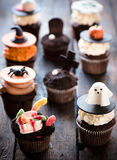Funny Halloween cup cakes. Funny cup cakes as Halloween decoration on the wooden background,selective focus Stock Photography