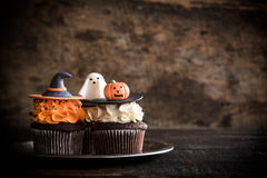 Funny Halloween cup cakes. Funny cup cakes as Halloween decoration on the wooden background,selective focus and blank space Royalty Free Stock Photo