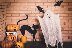 Funny Halloween decoration. Funny Halloween decoration with smiling ghost and pumpkins, black painted bats and cat on the brick wall background Royalty Free Stock Images