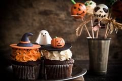 Funny Halloween desserts. Funny cup cakes and cake pops as Halloween decoration on the wooden background,selective focus Royalty Free Stock Image