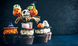 Funny Halloween desserts. Funny delicious cake pops and cup cakes for Halloween on the table,selective focus and empty space Royalty Free Stock Image