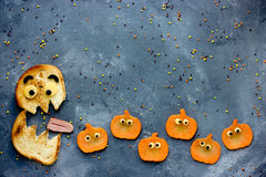 Funny Halloween food background bread monster eatsl pumpkin Stock Image