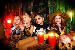 Funny halloween. Group of funny children dressed in halloween costumes in a wizarding lair. Halloween party royalty free stock photography