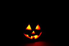 Funny Halloween pumpkin isolated on a black background glow from Royalty Free Stock Images