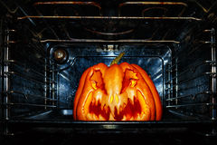 Funny Halloween pumpkin roasted in a dirty oven. Funny Halloween pumpkin roasted in a dirty black oven royalty free stock photo