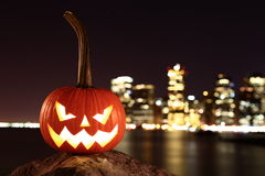 Funny Halloween's pumpkin. Scary pumpkin, symbol of Halloween, waiting for a celebrate on the shores of Brooklyn, against Manhattan Island, New York, United royalty free stock image