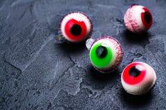 Jelly eyeballs on dark. Funny halloween treat - jelly eyeballs on dark background. Copy space Stock Image