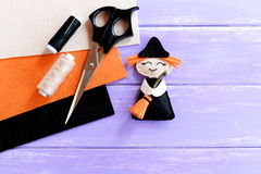 Funny Halloween witch made of felt, scissors, thread set, orange, beige and black felt sheets on wooden background royalty free stock images