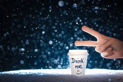 Funny hand with paper cup with tea on snow background; Royalty Free Stock Photo