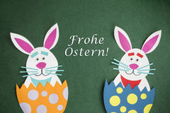 Funny handmade cartoon rabbits placed inside eggs with text in G Royalty Free Stock Images