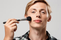 Funny handsome blond young man wearing casual plaid shirt with make-up brush looking in camera over grey background Royalty Free Stock Photo