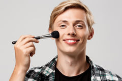 Funny handsome blond young man wearing casual plaid shirt with make-up brush looking in camera smiling over grey Royalty Free Stock Image