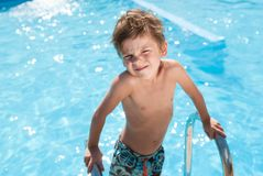 Funny handsome caucasian healthy little kid in blue fresh water pool in sunny summer day Royalty Free Stock Images