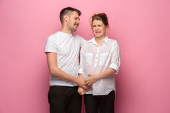 The funny handsome man and his beautiful pregnant wife`s tummy Stock Photo