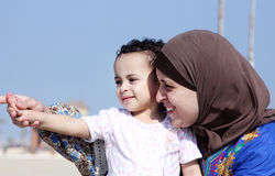 Funny happy arab muslim egyptian baby girl with her mother. Photo of funny happy arabian baby girl with her mother in local beach in egypt Royalty Free Stock Images