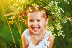 Funny happy baby child girl in a wreath on nature laughing in su Royalty Free Stock Photo