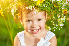 Funny happy baby child girl in a wreath on nature laughing in su Stock Image