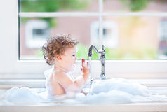 Funny happy baby girl in kitchen sink full with foam Royalty Free Stock Photos