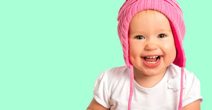 Funny happy baby girl in a pink  winter knitted hat laughing Stock Photos