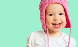 Funny happy baby girl in a pink winter knitted hat laughing. Funny happy baby girl child in a pink winter knitted hat laughing royalty free stock photography