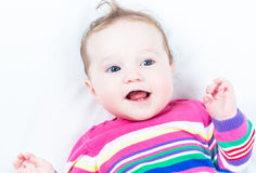 Funny happy baby girl wearing a pink knitted dress. On a white blanket Stock Image
