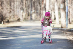 Funny happy beautiful pretty girl walking with toy pram Royalty Free Stock Images