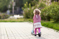 Funny happy beautiful pretty girl walking with toy pram Royalty Free Stock Photos
